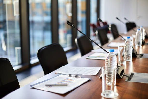 Business objects on table Business documents, plastic bottles of water, glasses and microphones along table and chairs near by in conference hall debate stock pictures, royalty-free photos & images