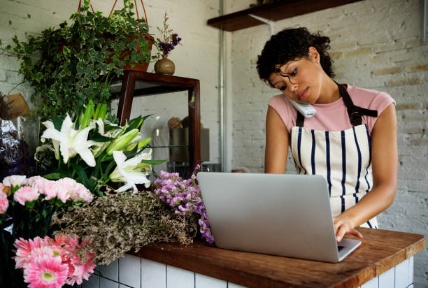 Business of flower shop with woman owner Business of flower shop with woman owner market vendor stock pictures, royalty-free photos & images