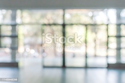 990877026 istock photo Business office corridor blur background interior view empty lobby hallway with glass wall white room and light bokeh 1145946056
