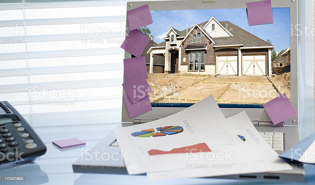 Business: Office desk, laptop showing home under construction royalty-free stock photo