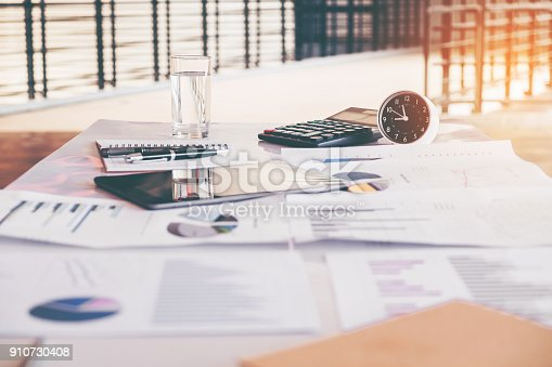 864278180istockphoto Business office equipment on the business paper. Report chart 910730408