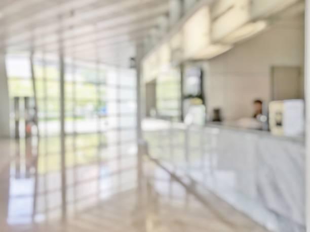 ビジネス オフィス ロビー銀行レセプション ホール顧客または患者のカウンター サービスの背景をぼかしし、ガラス壁とぼやけて病院、オフィスまたはホテル待っているホール内の机をレジ - 窓口 ストックフォトと画像