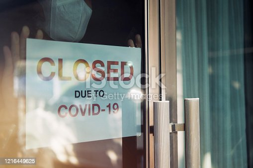 Business office or store shop is closed/bankrupt business due to the effect of novel Coronavirus (COVID-19) pandemic. Unidentified person wearing mask hanging closed sign in background on front door.