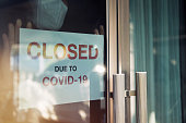 istock Business office or store shop is closed/bankrupt business due to the effect of novel Coronavirus (COVID-19) pandemic. Unidentified person wearing mask hanging closed sign in background on front door. 1216449625
