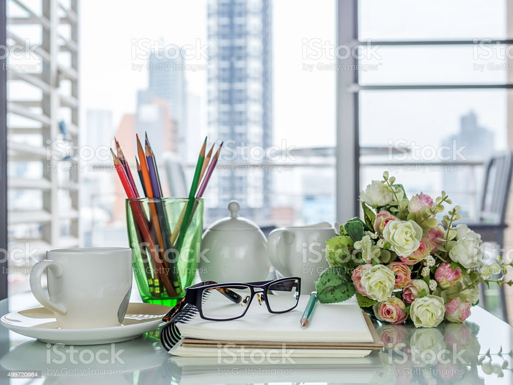 Business office scene with coffee cup, notebook on working table
