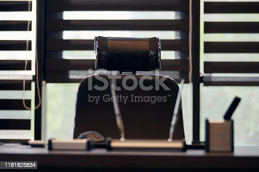 istock Business office workplace. Work place for chief, boss or other employees. Table and comfortable chair. Light through the half open blinds 1181825834