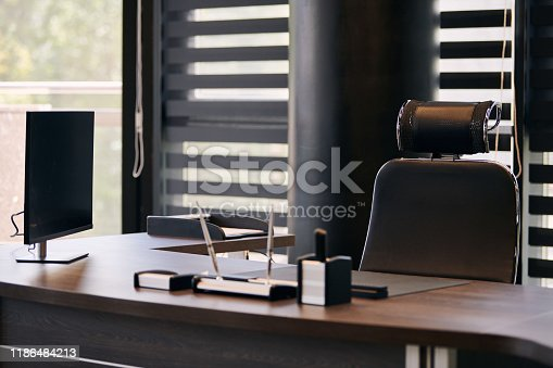 istock Business office workplace. Work place for chief, boss or other employees. Table and comfortable chair. Light through the half open blinds 1186484213
