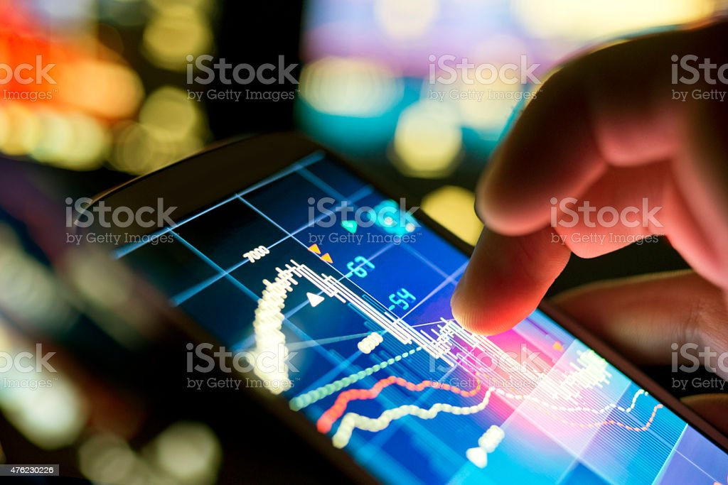 Business On The Go A businessman using a mobile phone to check stock market data. 2015 Stock Photo