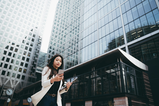 Smart Asian businesswoman managing her business with her smartphone in a financial area of the city.