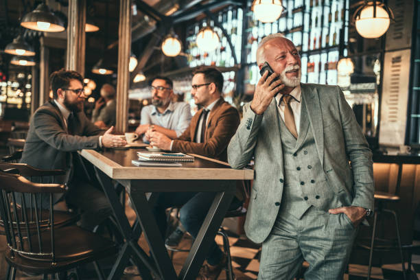 Business on the line Senior businessman talking on the phone in the pub old man working in a pub stock pictures, royalty-free photos & images