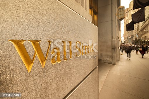 People walk by the New York Stock Exchange building in the financial district on Wall Street in lower Manhattan New York USA is home to one of the world's leading financial markets