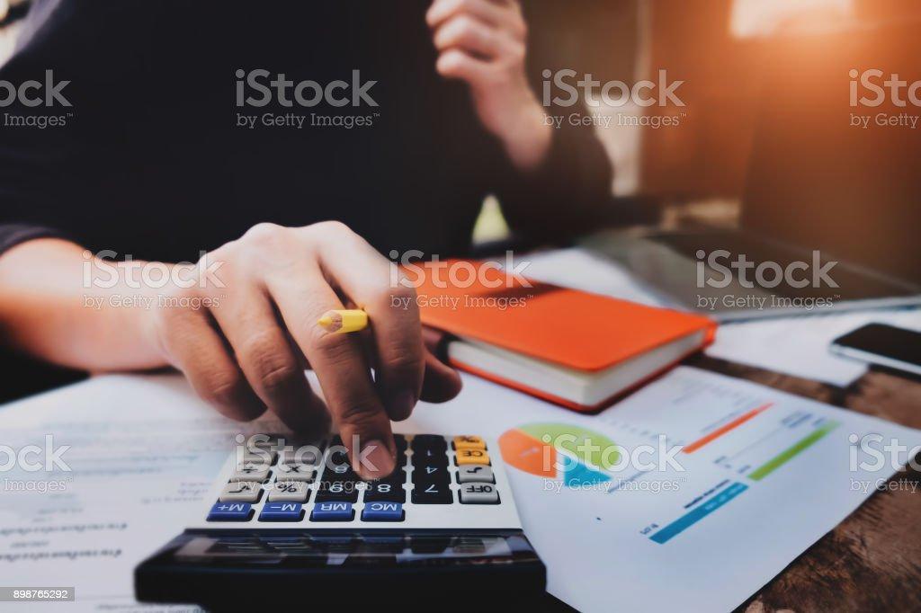 Geschäft oder Buchhalter Konzept, Mann, hält Stift mit Rechner für Berechnung finanzielle & Budget & Steuer Datendokument mit Notebook und Laptop-Computer bei der Bearbeitung von Holz Schreibtisch im Büro. – Foto