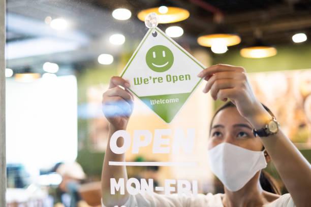 geschäftsinhaber asiatische frau tragen schützende gesichtsmaske ppe hängen offene zeichen an ihrem restaurant / café, wieder geöffnet nach sperrung wegen ausbruch des coronavirus covid-19 - offen allgemeine beschaffenheit stock-fotos und bilder