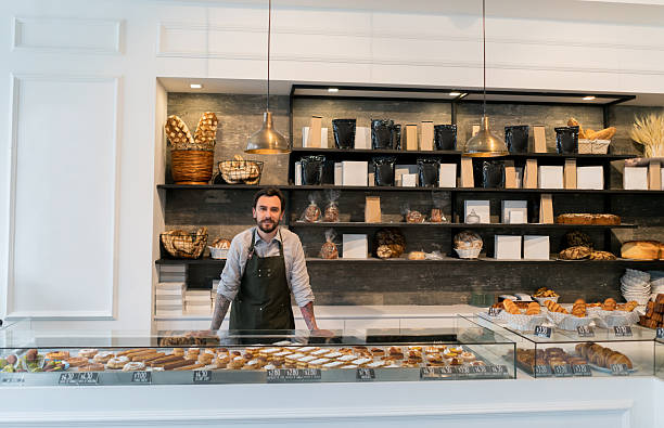 business owner at a bakery shop - bakeries stock photos and pictures