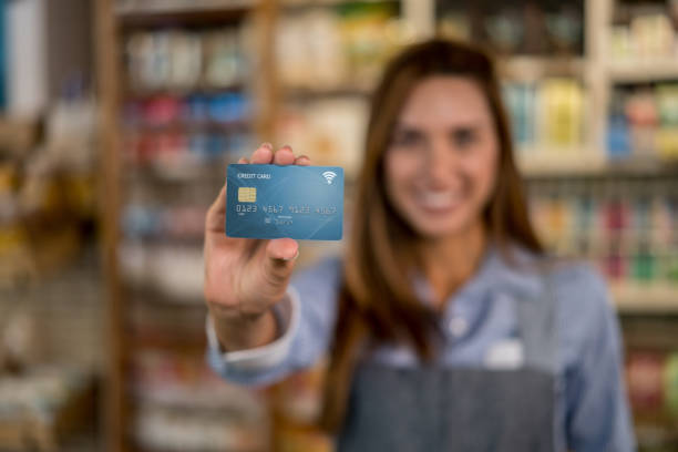 business owner at a food market holding a credit card - business credit card stock photos and pictures