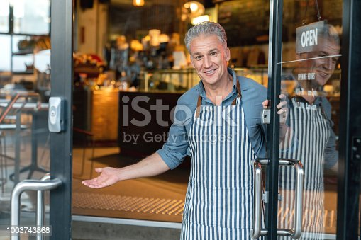 Business owner at the door of a cafe welcoming customers and looking very happy