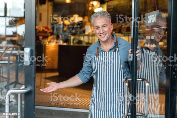 Business owner at the door of a cafe welcoming customers picture id1003743868?b=1&k=6&m=1003743868&s=612x612&h=qk0c anojnu25h i850l8yptccz00dag45bi2etqybo=