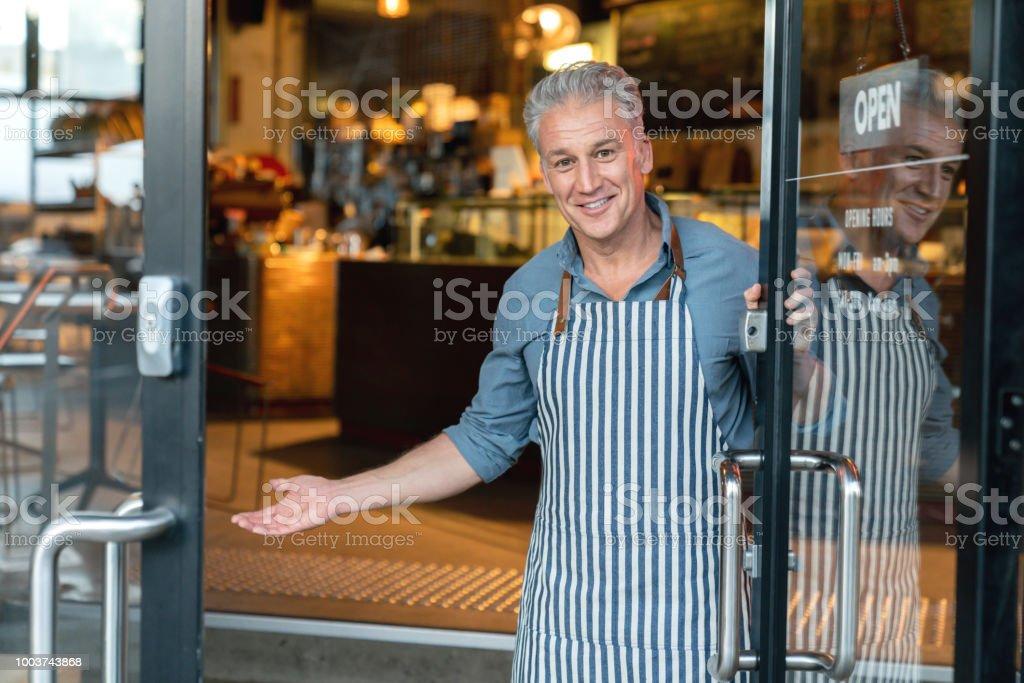 Geschäftsinhaber an der Tür eines Cafés begrüßen Kunden – Foto