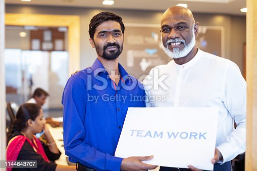 Corporate Business, Indian, Office - Business Executive standing besides his colleagues with a plaque stating