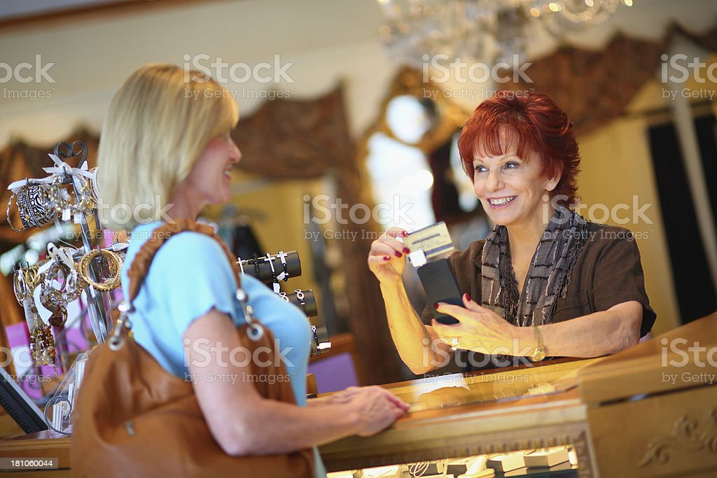 Business owner charging a customers card in store Senior Business Owner Using Credit Card Swiper on Mobile Phone 40-49 Years Stock Photo