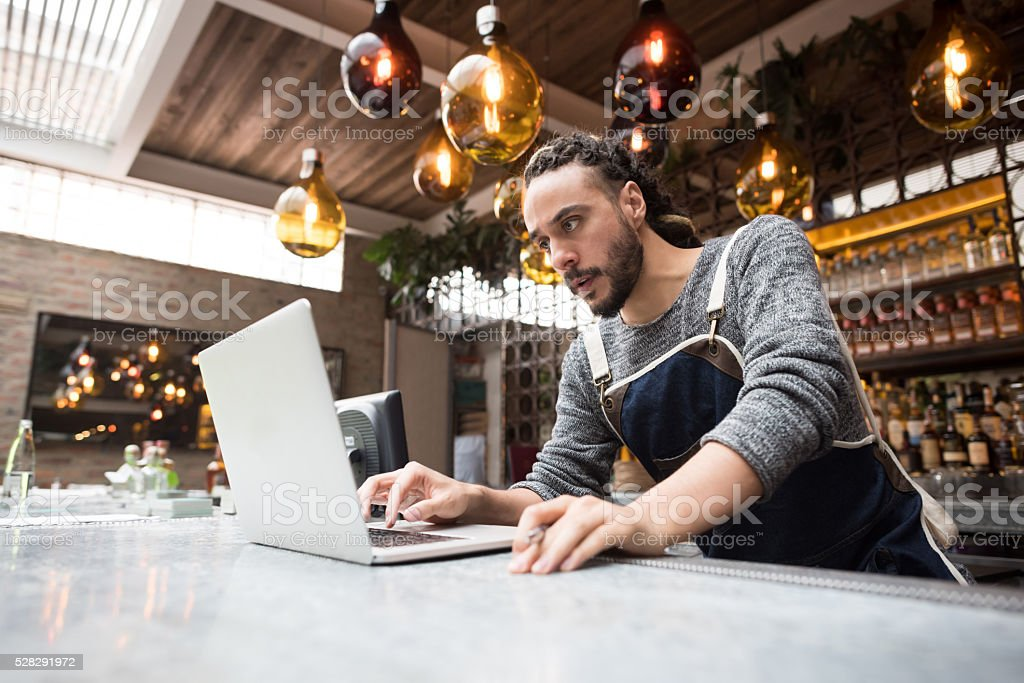 Business owner doing the books at a restaurant - foto stock