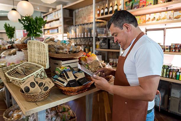 business owner doing the inventory at a grocery shop - einzelhandelsarbeiter stock-fotos und bilder