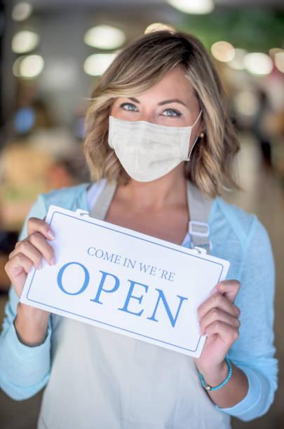 Geschäftsinhaber hält ein offenes Schild in einem Lebensmittelgeschäft und trägt eine Gesichtsmaske – Foto
