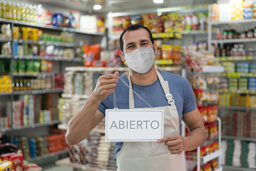 Portrait of a business owner holding an open sign (in Spanish) at a grocery store and wearing a facemask - quarantine lifestyle concepts