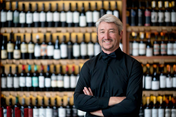 Business owner of a wine store looking at camera smiling with arms crossed stock photo