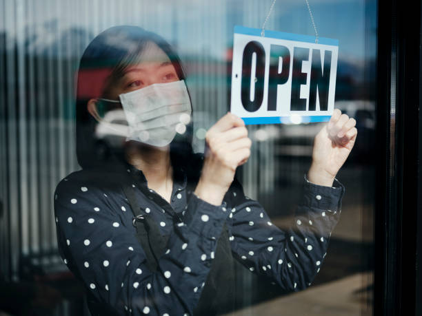 Business Owner Open Sign A business owner changing the store sign to OPEN after being closed for a period of time due to social distancing guidelines related to Coronavirus. east asian ethnicity stock pictures, royalty-free photos & images
