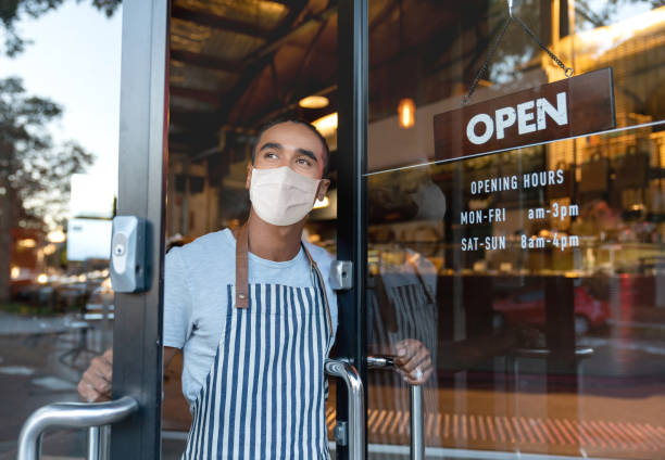 Business owner opening the door at a cafe wearing a facemask stock photo