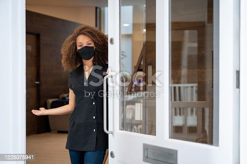 Business owner opening the door of her spa wearing a facemask to avoid the coronavirus – pandemic lifestyle concepts