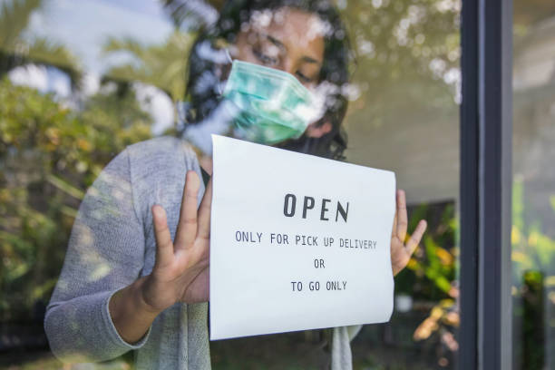 Business owner putting open sign only for pick up delivery and take away food during Covid 19 pandemic stock photo