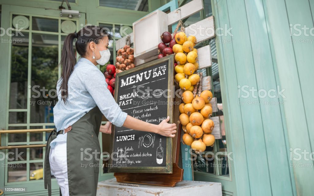 Business owner reopening a restaurant while wearing a facemask Latin American business owner reopening a restaurant after quarantine and placing the menu board while wearing a facemask Apron Stock Photo