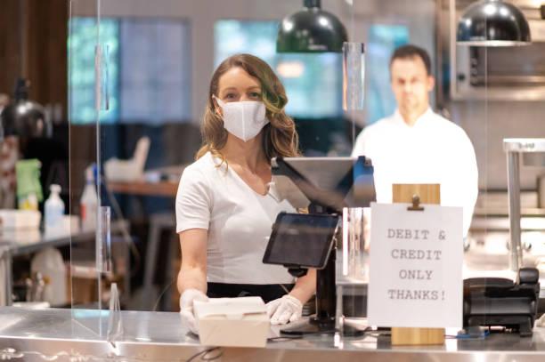 Geschäftsinhaber, der Kunden in einem Post-COVID-Geschäft betreut – Foto