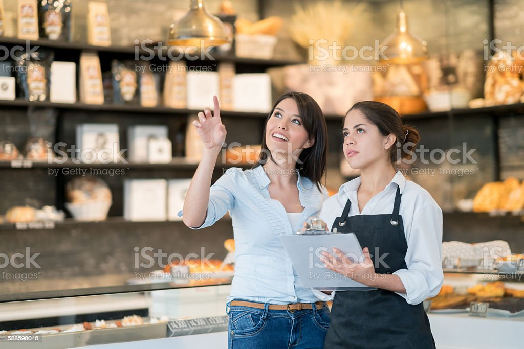 Business owner talking to manager at a bakery stock photo