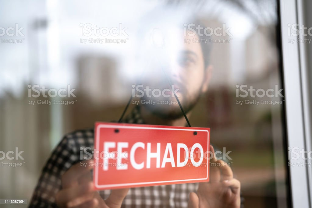 Business owner turning as closed for business sign in their...