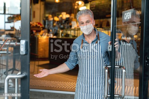 Business owner wearing a facemask and reopening his cafe after the quarantine - COVID-19 lifestyle concepts