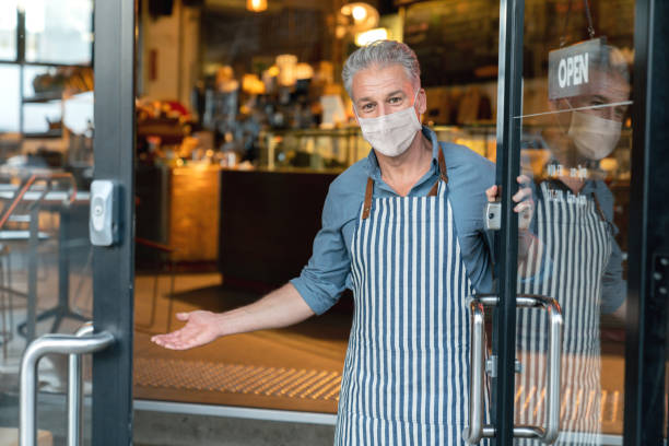 business owner wearing a facemask and reopening his cafe after the quarantine - small business owner stock pictures, royalty-free photos & images