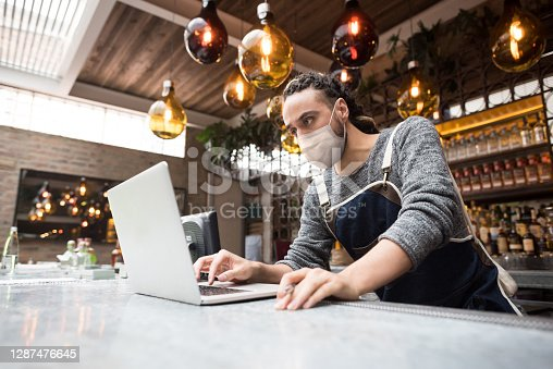 Business owner wearing a facemask at a restaurant and doing the books using a laptop computer - COVID-19 concepts