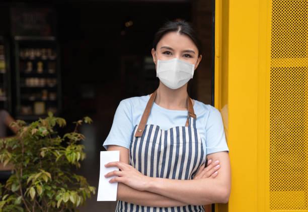 Geschäftsinhaber arbeitet in einem Café mit Einer Gesichtsmaske – Foto