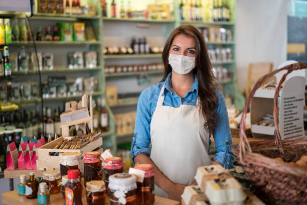 Business owner working at a convenience store wearing a facemask stock photo