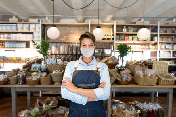 Geschäftsinhaber arbeitet in einem Lebensmittelgeschäft mit einer Gesichtsmaske – Foto