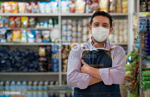 Business owner working at a grocery store wearing a facemask to avoid the coronavirus - pandemic lifestyle concepts