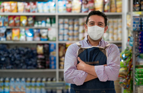 business owner working at a grocery store wearing a facemask - small business owner stock pictures, royalty-free photos & images