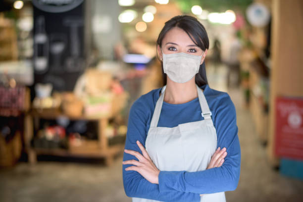 Business owner working at a supermarket wearing a facemask stock photo