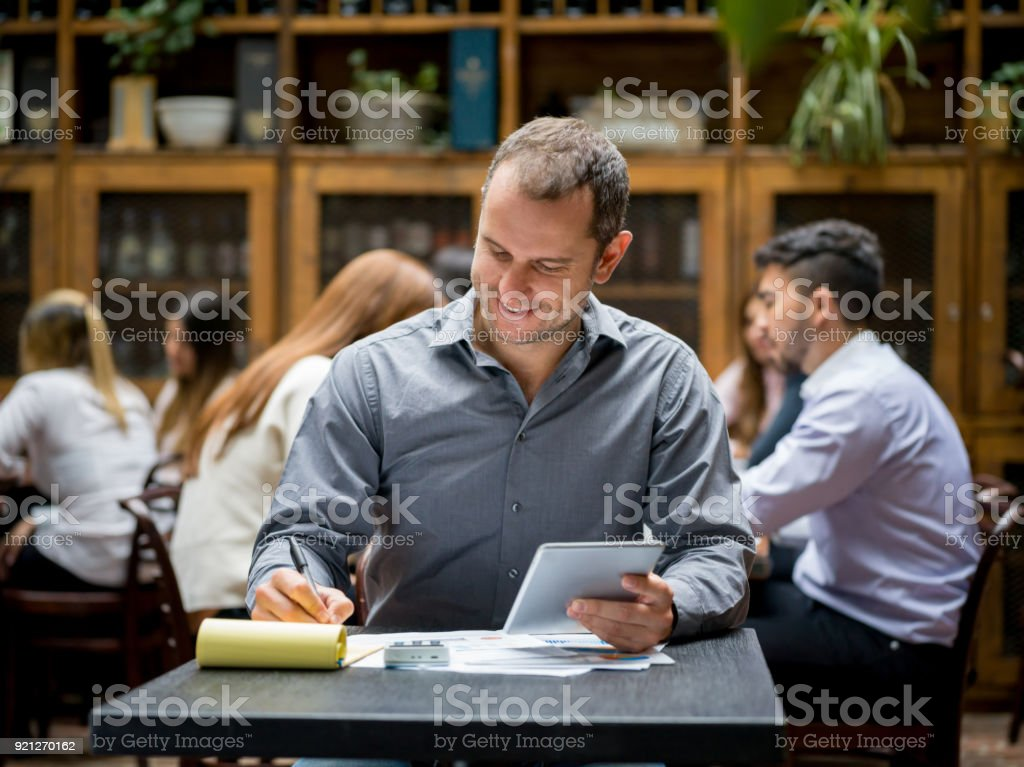 Business owner working at his restaurant keeping the books stock photo