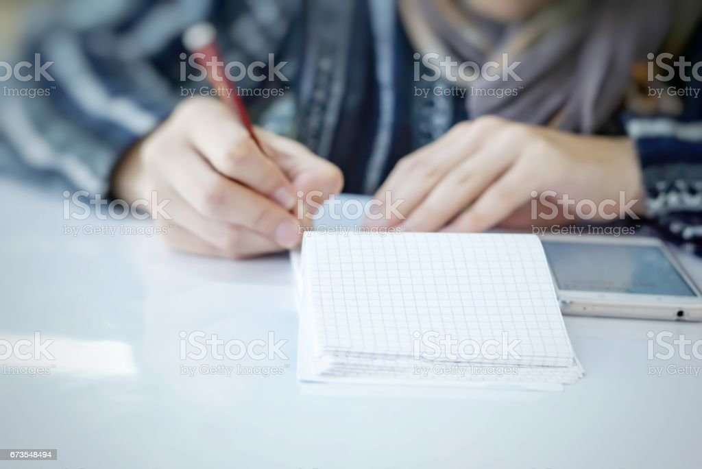 business owner writing down his monthly accounting with a smartphone royalty-free stock photo
