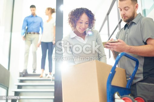 a female office worker takes delivery of business parcels in a brightly lit office. She checks the packages as the courier taps on his pda for her to sign. In the background two co-workers are coming down the stairs chatting as they go .