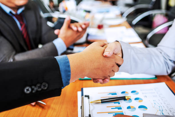 Business partner colleagues shake hands on meeting in modern office discussing management project. stock photo